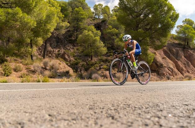 Chłopiec na rowerze na rowerze szosowym na zewnątrz na drodze z drzewami w tle