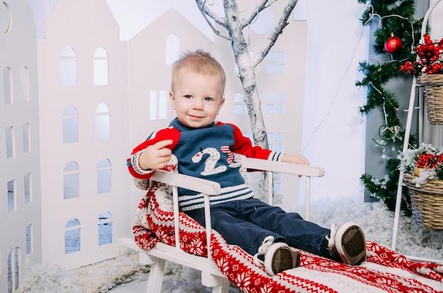 Chłopiec na saniach. mały chłopiec siedzi w drewniane sanki zdobione, w zimowym wnętrzu.
