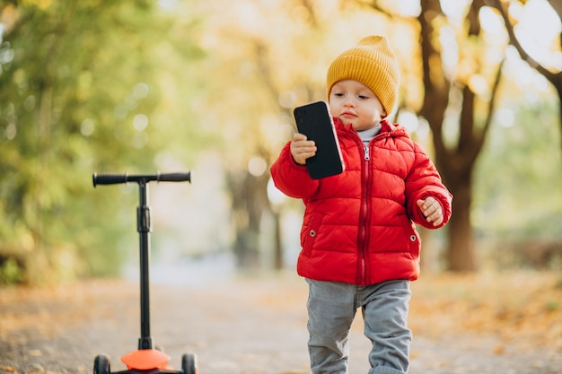Chłopiec na skuterze trzyma telefon komórkowy w jesiennym parku