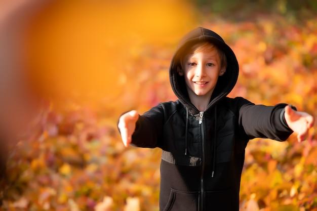 Chłopiec na tle jesiennego parku żółty.