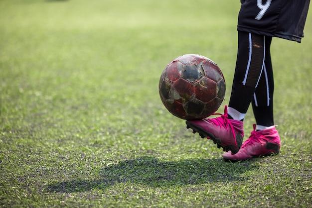 Chłopiec na treningu piłkarskim, umiejętności z piłką nożną w lokalnej tajlandii