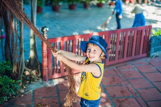 Chłopiec na wietnamie podróżnik jest w tle piękne drzewo z powietrznymi korzeniami