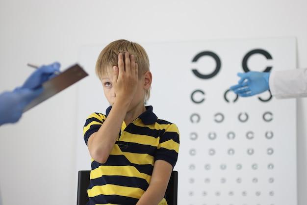 Chłopiec na wizycie u okulisty zamyka jedno oko i odpowiada na pytania.