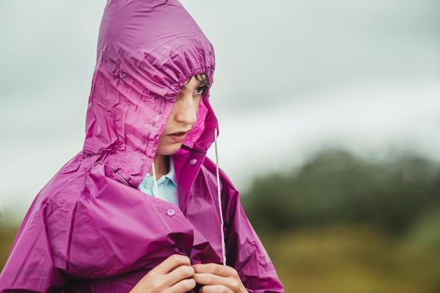 Chłopiec na zewnątrz ubrany w płaszcz przeciwdeszczowy, aby nie zmoknąć wodą deszczową
