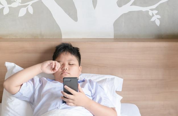 Chłopiec naciera oczy po bawić się smartphone