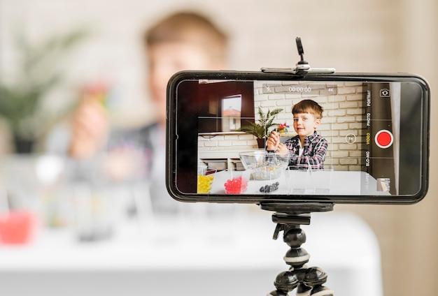 Chłopiec nagrywa się ze smartfonem