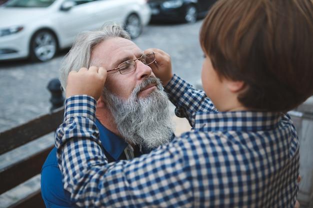 Chłopiec nakłada okulary na twarz swojego dziadka