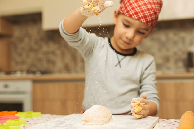 Chłopiec nalewa ciasto z mąką.