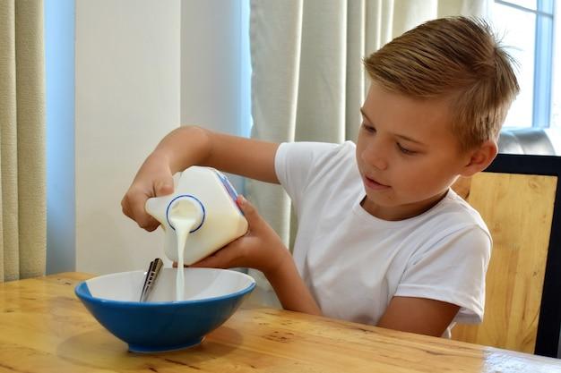 Chłopiec nalewa mleko do talerza. płatki kukurydziane rano