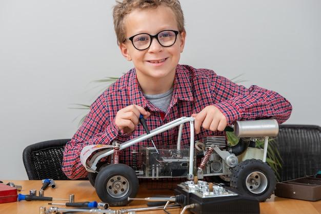 Chłopiec naprawia wzorcowego radiowego samochód w domu