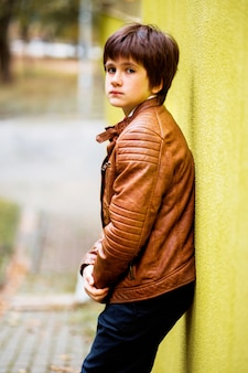 Chłopiec nastolatek pozuje przeciw żółtemu ściennemu tłu