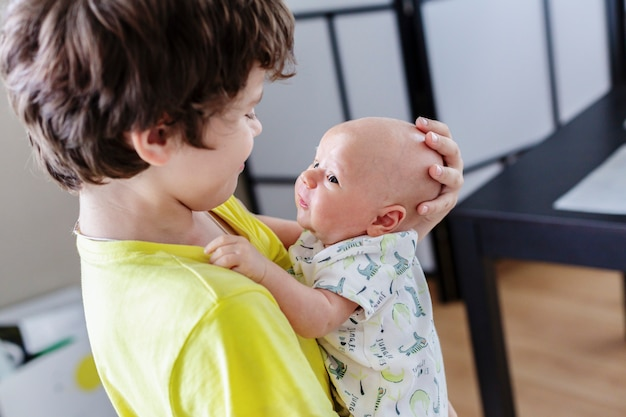 Chłopiec nastolatek trzyma w rękach chłopca i uśmiecha się, patrząc na swojego młodszego brata. starszy brat bawi się z uroczym noworodkiem