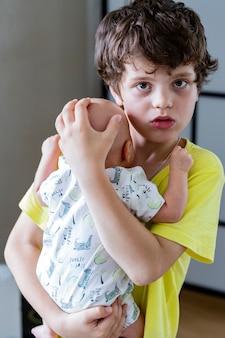 Chłopiec nastolatek trzyma w rękach chłopca i wygląda na zaniepokojonego i zrozpaczonego. starszy brat opiekuje się młodszymi.