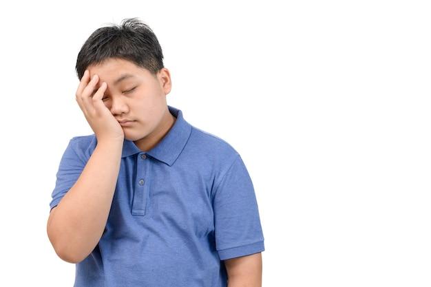Chłopiec nosić niebieską koszulkę polo znudzony lub spać na białym tle na białym tle, koncepcja emocji