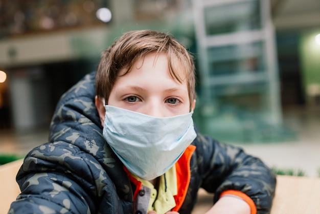 Chłopiec noszący medyczną maskę na twarz, głęboko zamyślony, środki ochronne przed rozprzestrzenianiem się covid-19