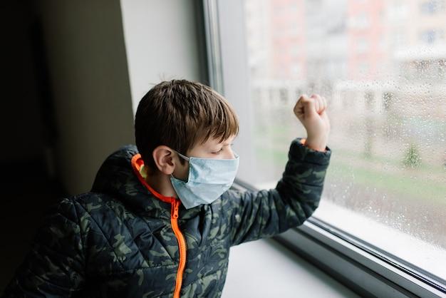 Chłopiec noszący medyczną maskę na twarz, środki ochronne przed rozprzestrzenianiem się covid-19