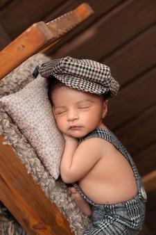 Chłopiec noworodek śpi na brązowym drewnianym łóżku w małym garniturze i kapeluszu