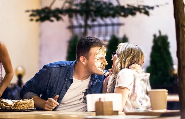 Chłopiec o brudnej twarzy z bitą śmietaną szczęśliwie rozmawia z blondynką