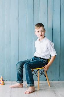 Chłopiec obsiadanie na krześle podczas przyjęcia urodzinowego