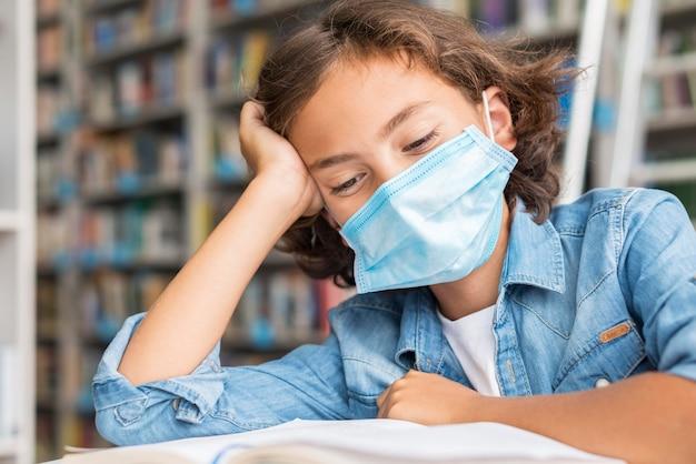 Chłopiec odrabia lekcje nosząc maskę medyczną