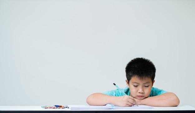 Chłopiec odrabiania lekcji, papier do pisania dla dzieci, koncepcja edukacji, powrót do szkoły