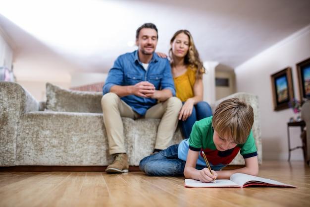 Chłopiec odrabiania lekcji, podczas gdy rodzice siedzą na kanapie