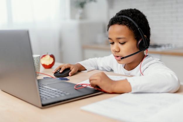 Chłopiec odrabiania lekcji z wykorzystaniem laptopa