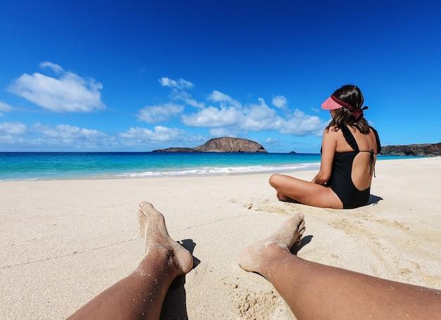 Chłopiec ogląda dziewczyny siedzi wpólnie na plaży