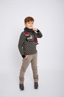 Chłopiec ono uśmiecha się i pozuje na białym tle w studiu, modzie i odziewa.