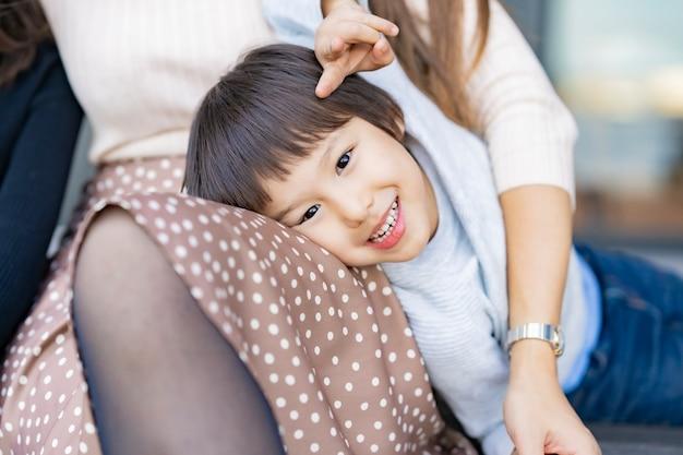 Chłopiec oparty o swoją mamę i uśmiechnięty