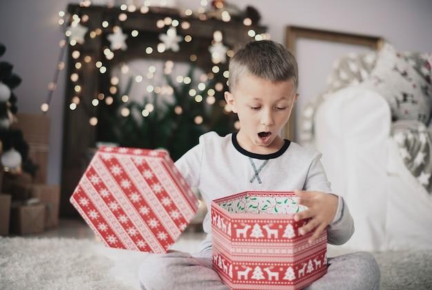 Chłopiec otwiera prezent na boże narodzenie w domu
