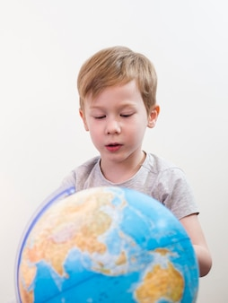 Chłopiec patrzeje na kuli ziemskiej