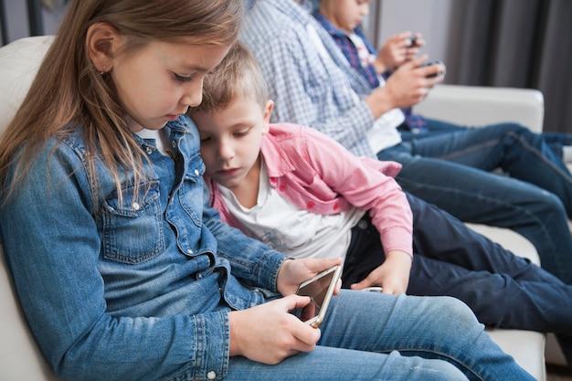 Chłopiec patrzeje siostrzanego używa smartphone