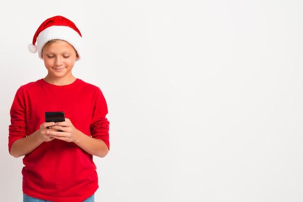 Chłopiec patrzeje telefon kopii przestrzeń