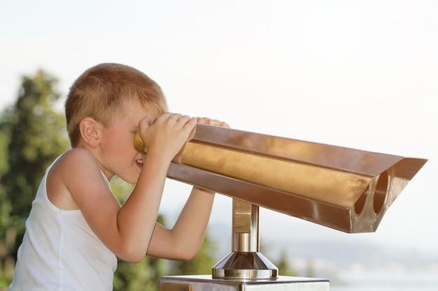 Chłopiec patrzy na duże lornetki