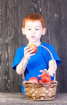 Chłopiec patrzy na nektarynę, którą trzyma w dłoni, na stole jest kosz z innymi nektarynkami i brzoskwiniami