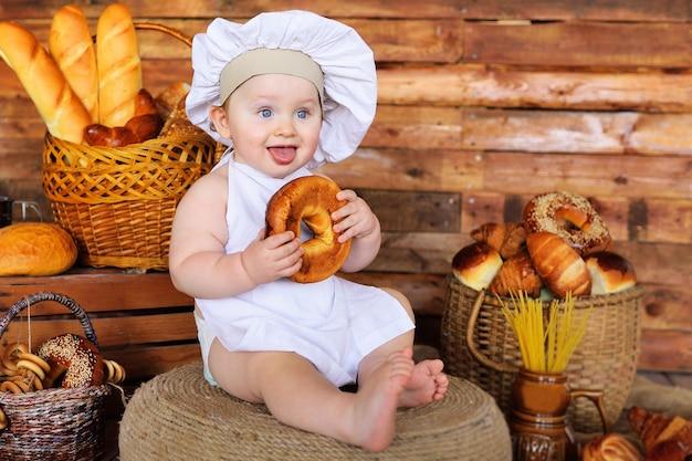 Chłopiec piekarz w kapeluszu i fartuchu szefa kuchni z dużym bajglem w dłoniach uśmiecha się na tle produktów piekarniczych