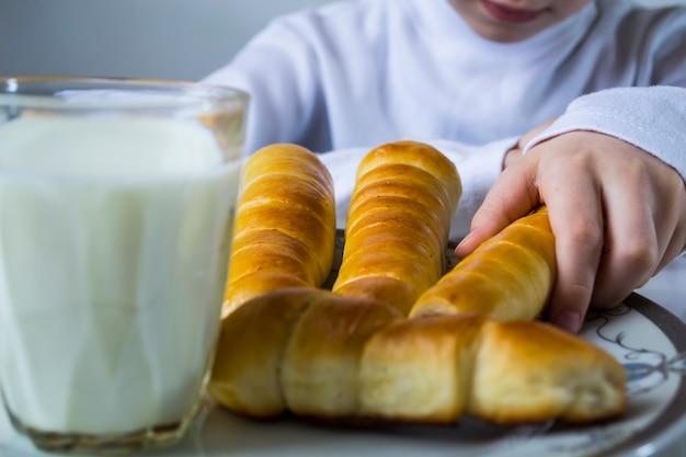Chłopiec pije mleko i je kiełbasę w cieście