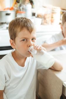 Chłopiec pije mleko z butelki w domowej kuchni. rano śniadanie z mlekiem. szczęśliwe dziecko w białej koszulce pije mleko z butelki