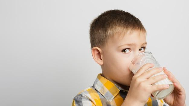 Chłopiec pije mleko z szkłem