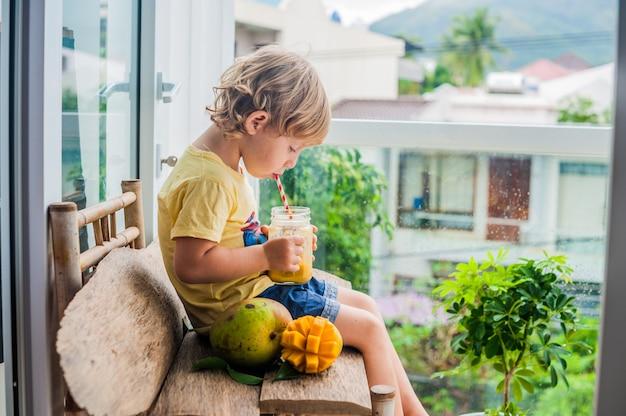 Chłopiec pije soczysty koktajl z mango w szklanym słoiku z pasiastą czerwoną słomką