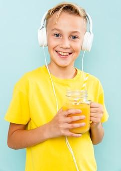 Chłopiec pije sok pomarańczowego z hełmofonami