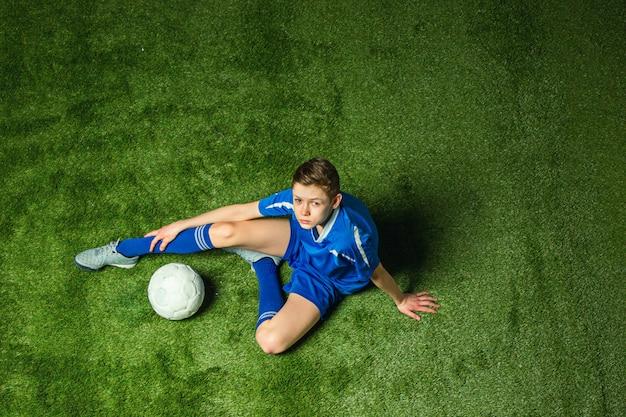 Chłopiec piłkarz siedzi na zielonej trawie