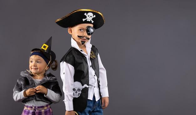 Chłopiec pirat i mała czarownica na halloween. dzieci w kostiumach karnawałowych na szarej ścianie z wolną przestrzenią boczną.