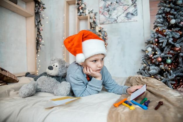 Chłopiec pisze do świętego mikołaja. świąteczny wieczór rodzinny. prezenty noworoczne. urządzony jasny salon