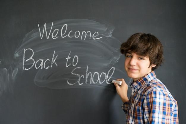 Chłopiec pisze do szkoły na czarnej tablicy