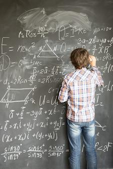 Chłopiec pisze kredą skomplikowane wzory matematyczne na czarnej tablicy