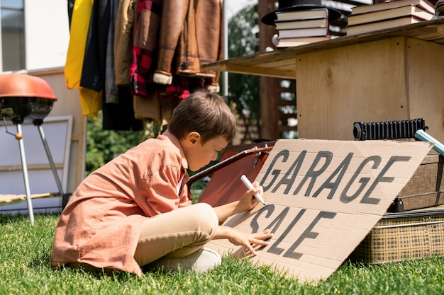 Chłopiec pisze na banerze kartonu