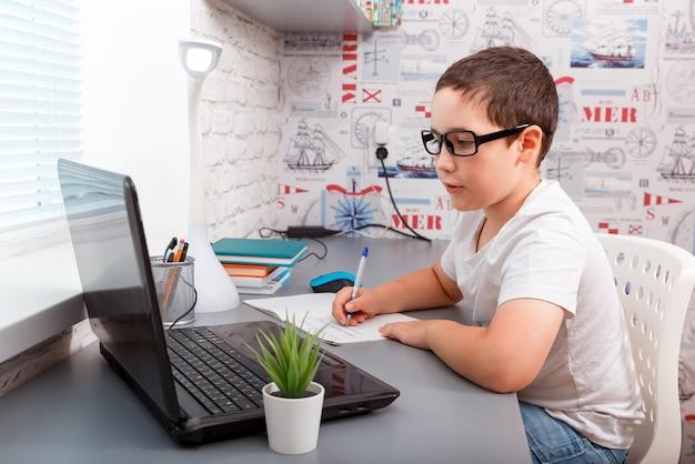 Chłopiec pisze w zeszycie i uśmiecha się podczas odrabiania lekcji
