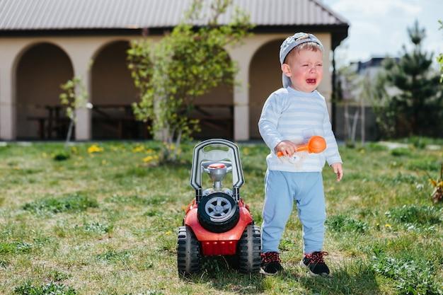 Chłopiec płacze blisko zabawkarskiego samochodu